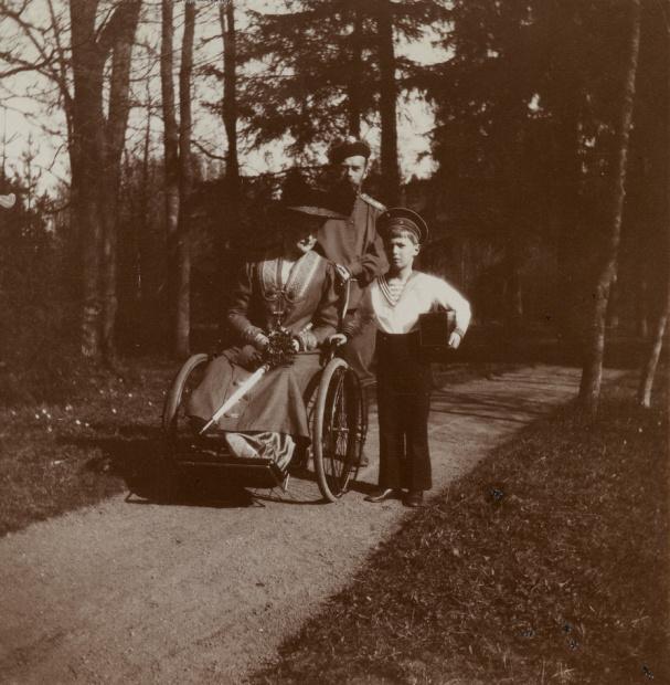 Empress Alexandra Feodorovna, Emperor Nicholas II, and Tsesarevich Alexei (holding camera), in the Alexander Park. c. 1910s
